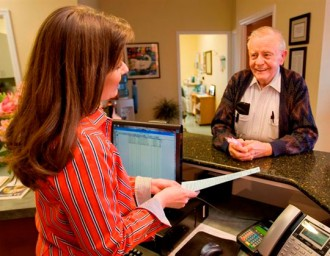 Get Help: senior man talking to receptionist in office