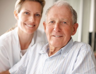 Senior man smiling with nurse in background