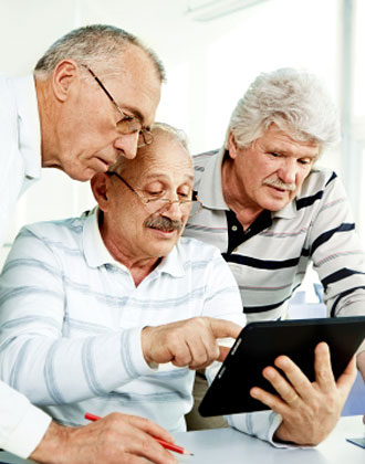 Three senior men looking at computer